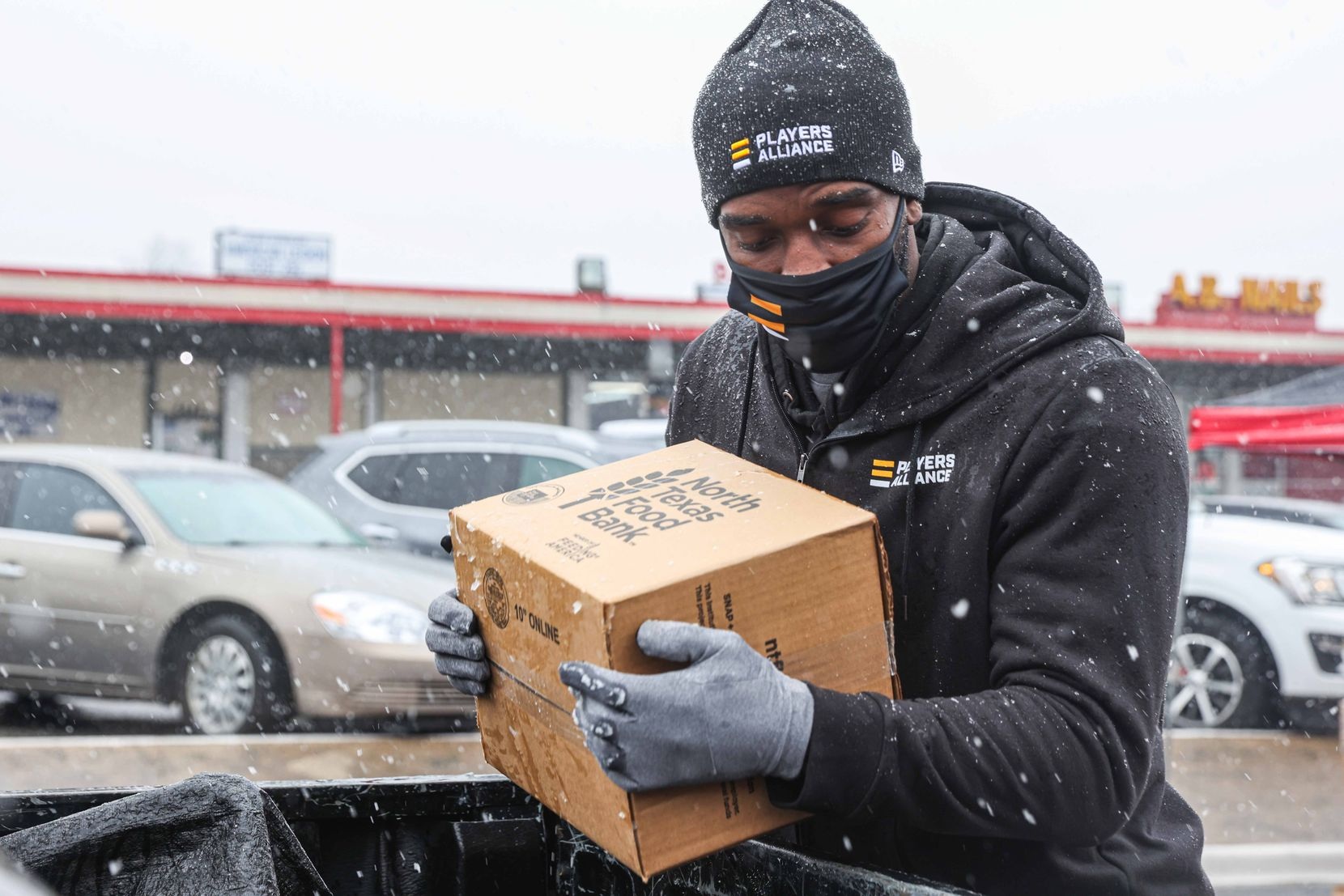 Rangers pitcher Taylor Hearn, places a box of food in the truck of a car as part of the donations made by the MLB Players Alliance in Oak Cliff on Sunday, January 10, 2021.