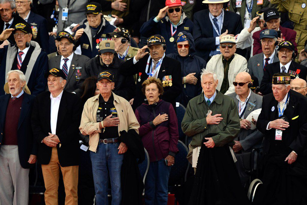 American World War II veterans listen to their national anthem during a French-U.S. ceremony at the Normandy American Cemetery and Memorial in Colleville-sur-Mer, Normandy, northwestern France, on June 6, 2019.