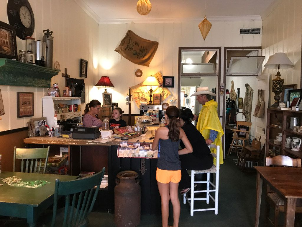 Customers gather at The Shop Downtown in Schulenburg, Texas, where Christine Heinrich, left, opened up to get a break from the monotony of a rainy weekend. Schulenburg was mostly spared from severe flooding, although Heinrich's home outside town did lose power. (Charles Scudder/Staff)