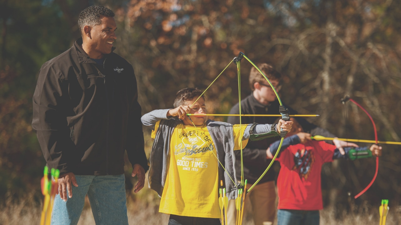 A group of scouts learns how to use a bow and arrow with their chaperones.