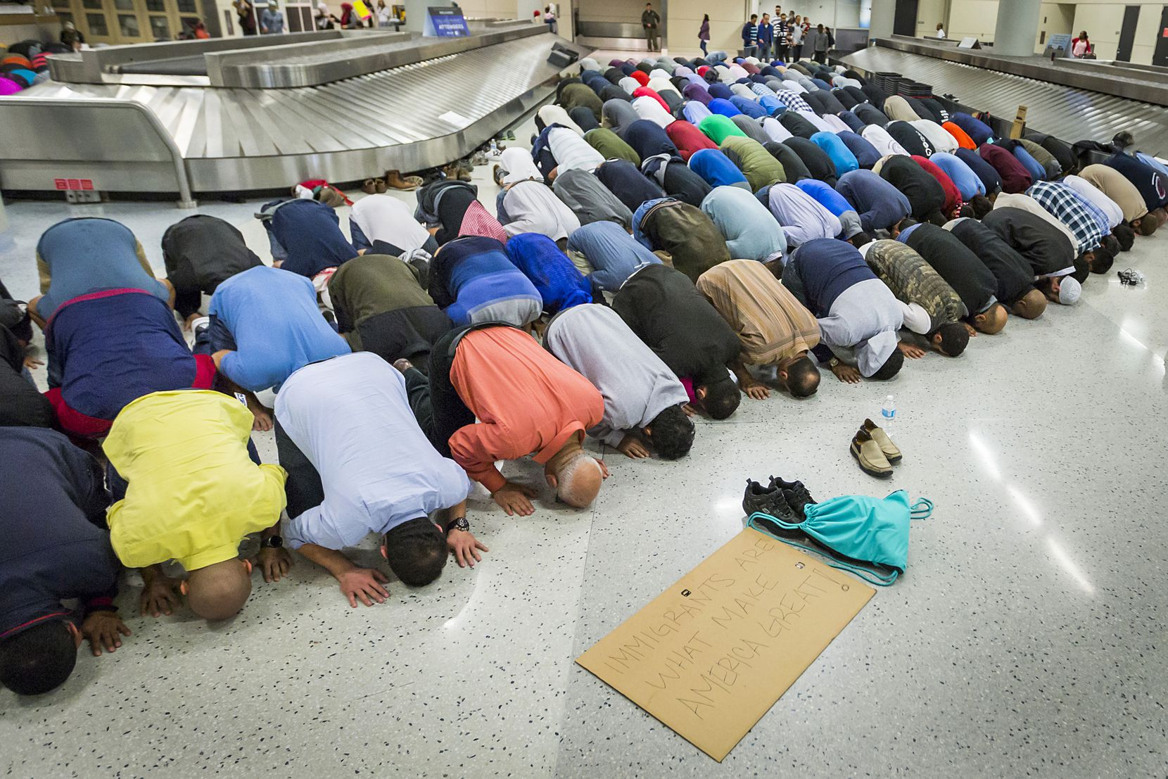 Muslim men set down their protest signs to pray at DFW International Airport where they gathered in opposition to President Donald Trump's executive order barring certain travelers on Sunday, Jan. 29, 2017. Multiple travelers were detained at DFW after Trump shut borders.