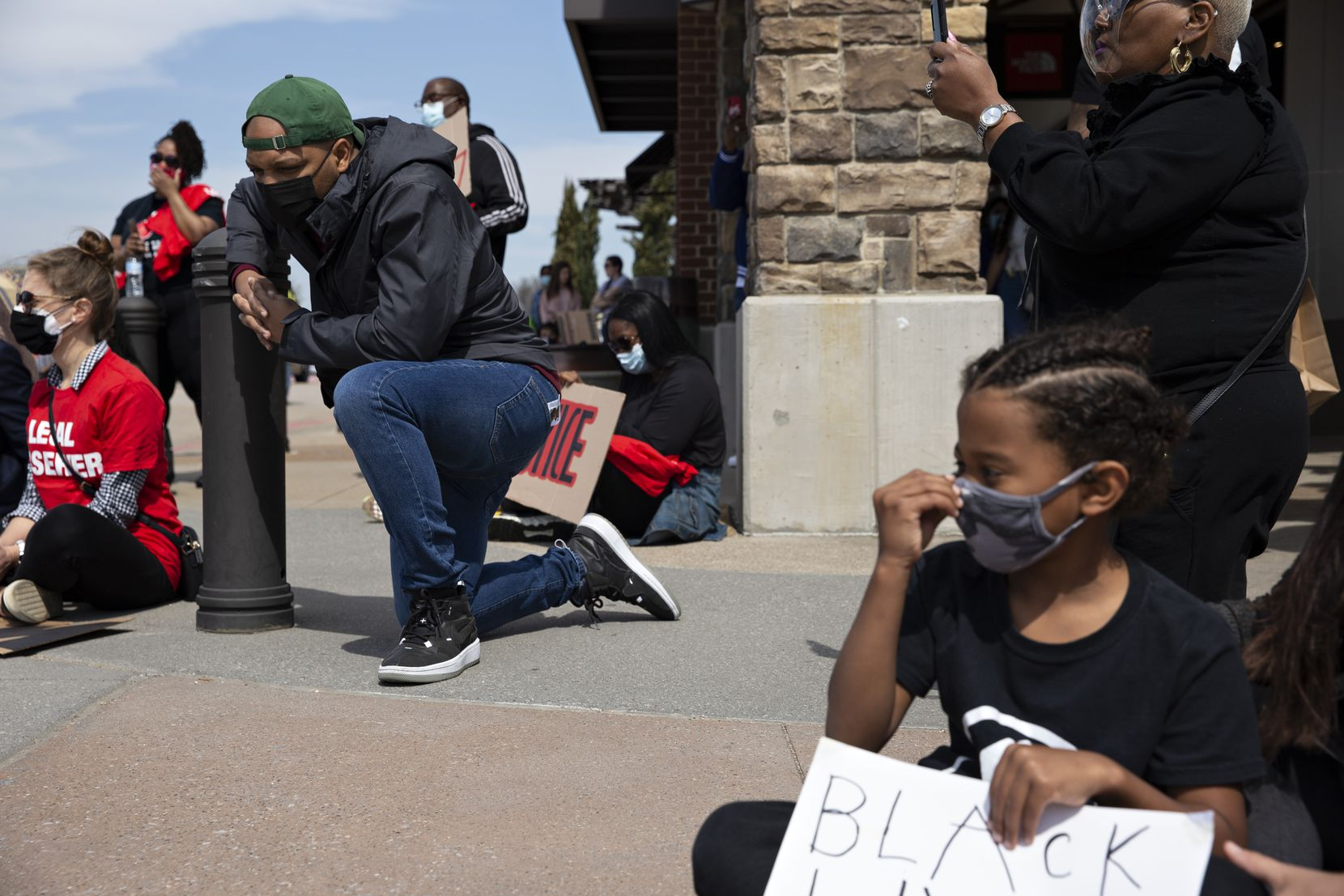 Carl Sherman Jr. takes a knee at the Allen Outlets on Sunday, March 21, 2021 during a march demanding justice for Marvin Scott III, who died a week prior while in custody at the Collin County Jail on March 14, 2021. Some patrons who were originally shopping at the outlets saw the march and joined as it circled the outlets multiple times. Demonstrators called for the arrest of the ÒCollin County SevenÓ, the seven Collin County Jail employees who were placed on leave after MarvinÕs death. (Shelby Tauber/Special Contributor)