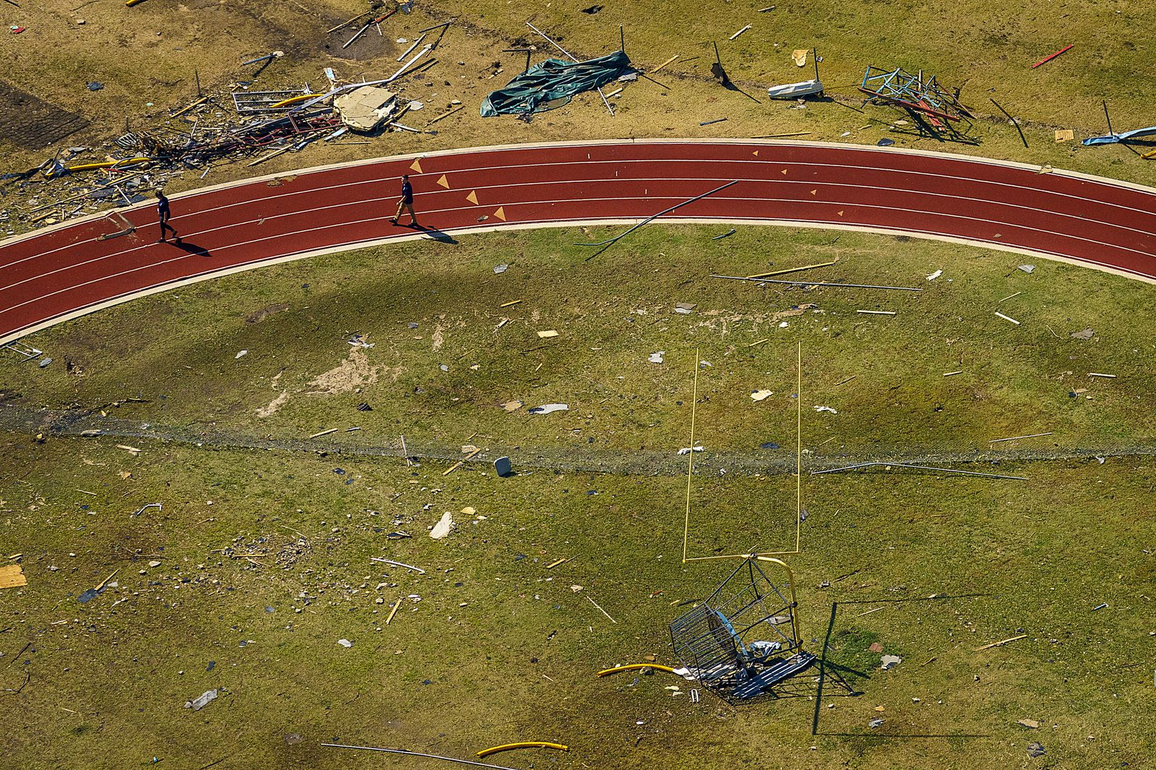 Rubble from tornado damage is strewn across an athletic field at Thomas Jefferson High School on Monday, Oct. 21, 2019, in Dallas.