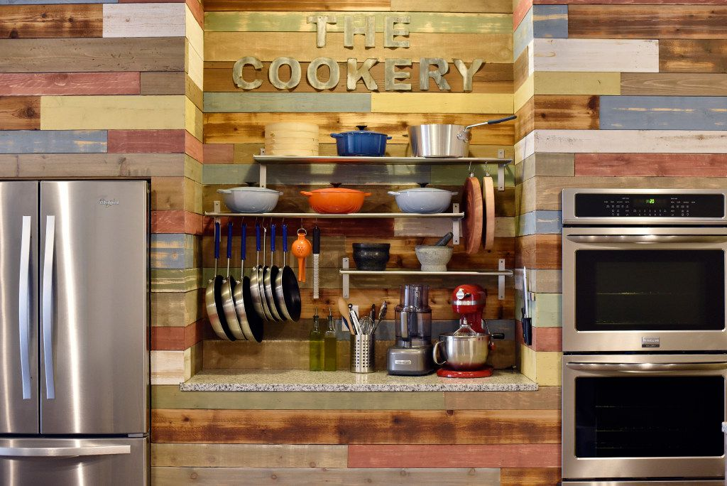 Cookware is stored on a countertop between the refrigerator and oven at The Cookery.