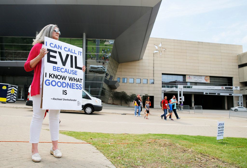 """Carol Shelton of Fort Worth holds up a sign as people begin to gather for the """"For Such A Time As This Rally,"""" outside of the Kay Bailey Hutchison Dallas Convention Center during the 2018 Annual Meeting of the Southern Baptist Convention in Dallas on Tuesday, June 12, 2018. (Vernon Bryant/The Dallas Morning News)"""