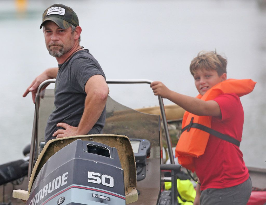 Chad White and his son John watched with satisfaction as residents of Meyerland made it to dry ground thanks to their efforts, and boat, during flooding on Loop 610 south near the Post Oak exit in Houston. (Louis DeLuca/Staff Photographer)