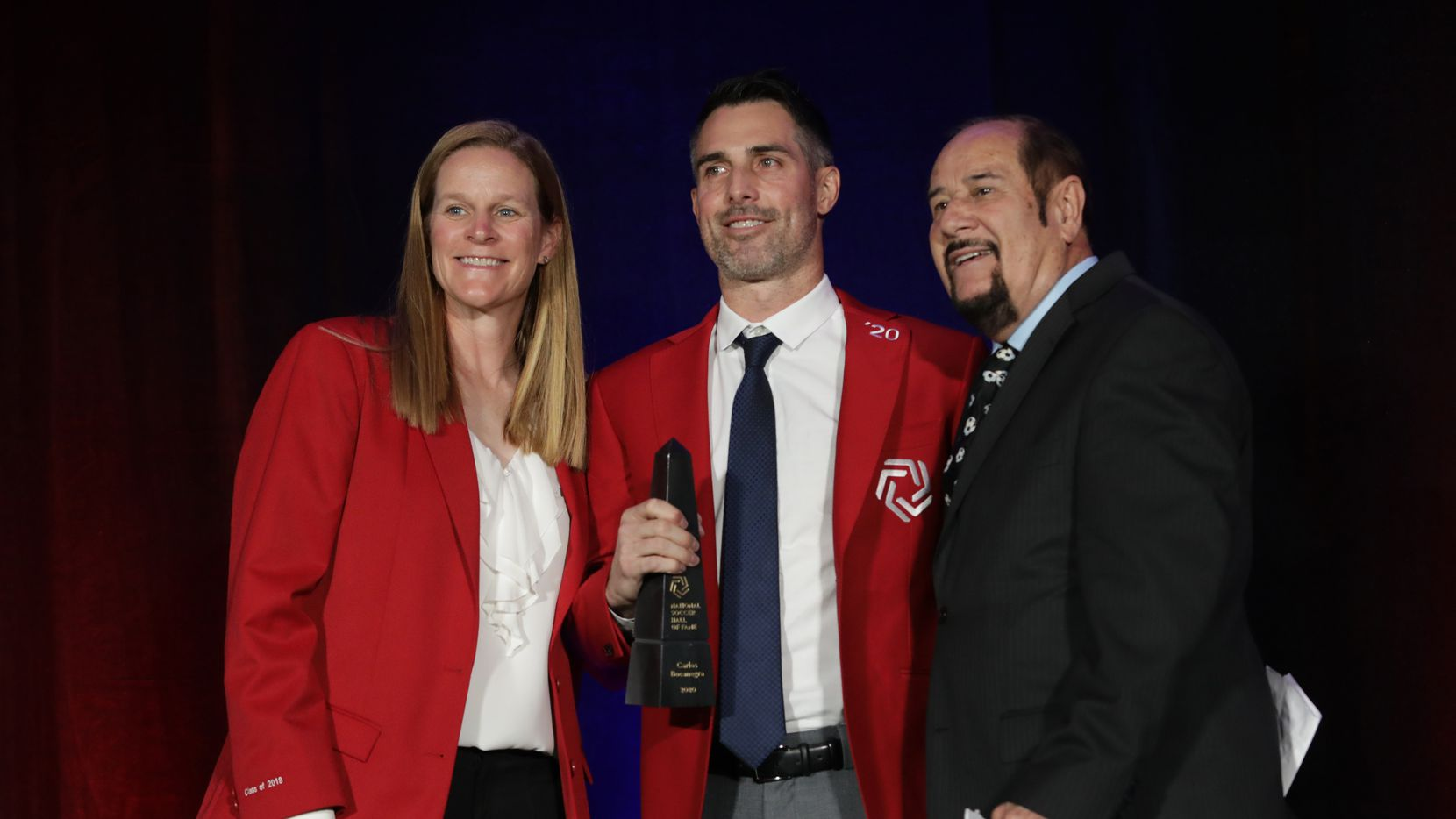 Cindy Parlow Cone, left, Carlos Bocanegra, and Manuel Bocanegra pose during the National Soccer Hall of Fame Induction ceremony at The Soccer Hall of Fame in Frsico, TX, on Oct. 2, 2021.