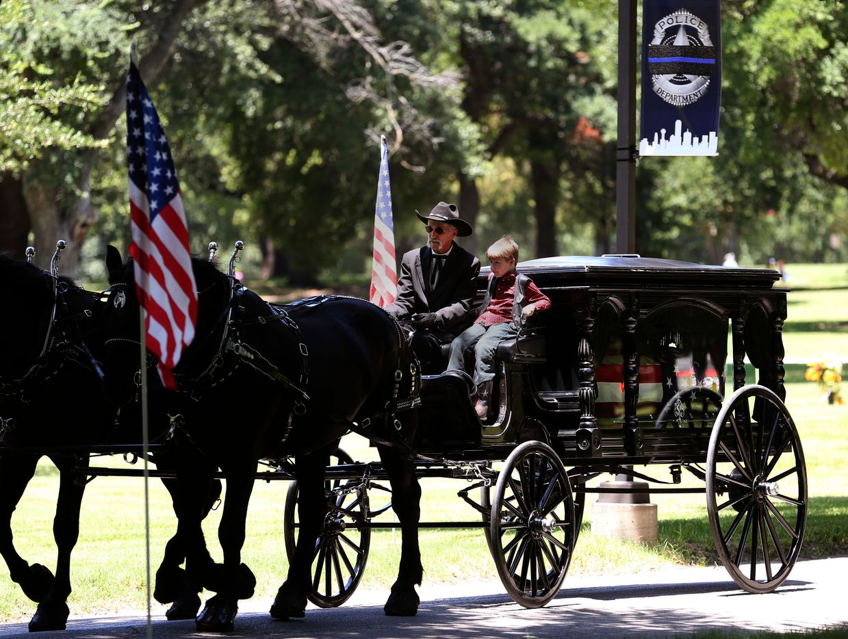 Magnus Ahrens, 8, son of fallen Dallas police officer Lorne Ahrens, rides with the caisson driver for his father's casket during the burial service at Restland Funeral Home and Cemetery in Dallas on July 13, 2016. Ahrens and four other officers were gunned down during an ambush on police in downtown Dallas.