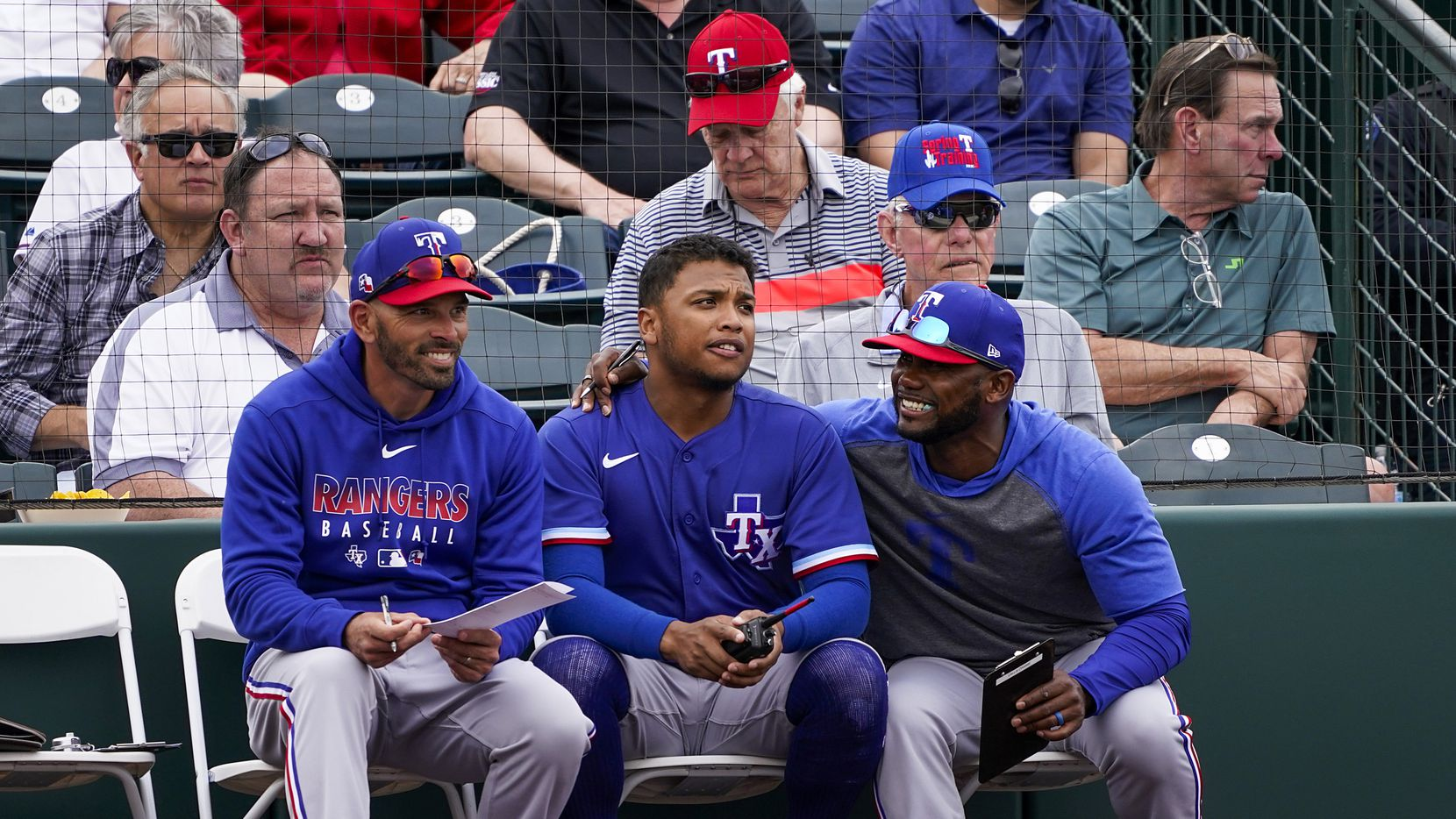 Texas Rangers outfielder Willie Calhoun (center) talks with assistant hitting coach Callix Crabbe (right) and manager Chris Woodward before batting during the fifth inning of a spring training game against the Los Angeles Angels at Tempe Diablo Stadium on Friday, Feb. 28, 2020, in Tempe, Ariz.