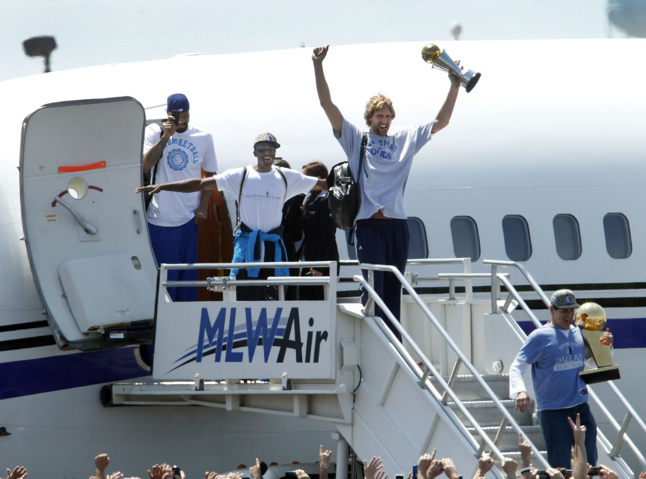 Dallas Mavericks owner Mark Cuban (bottom right) holds the Larry O'Brien NBA Championship trophy, followed by Dallas Mavericks Dirk Nowitzki holding the Bill Russell NBA Finals MVP trophy, Jason Terry doing his jet maneuver, and Tyson Chandler with his mobile phone, deplane after arriving at Dallas Love Field to the cheers of thousands of fans Monday, June 13, 2011 in Dallas. The Dallas Mavericks were returning home after defeating the Miami Heat the night before to become the 2011 NBA champions. (Jim Mahoney/The Dallas Morning News) 06162011xQUICK