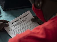 A man receives resources from attorneys with Legal Aid of Northwest Texas at the Justice of the Peace and Justice Courts in southern Dallas on June 28. The group offers assistance to defendants facing eviction.