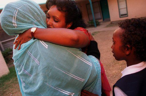 Safia Ismael, a Somali woman who  lives in Lewisville, gets a hug from newly arrived Somli refugee Nadifo Abshar, a single mother with children, after Safia came by  to check on how she and her family were getting along in their  new apartment.