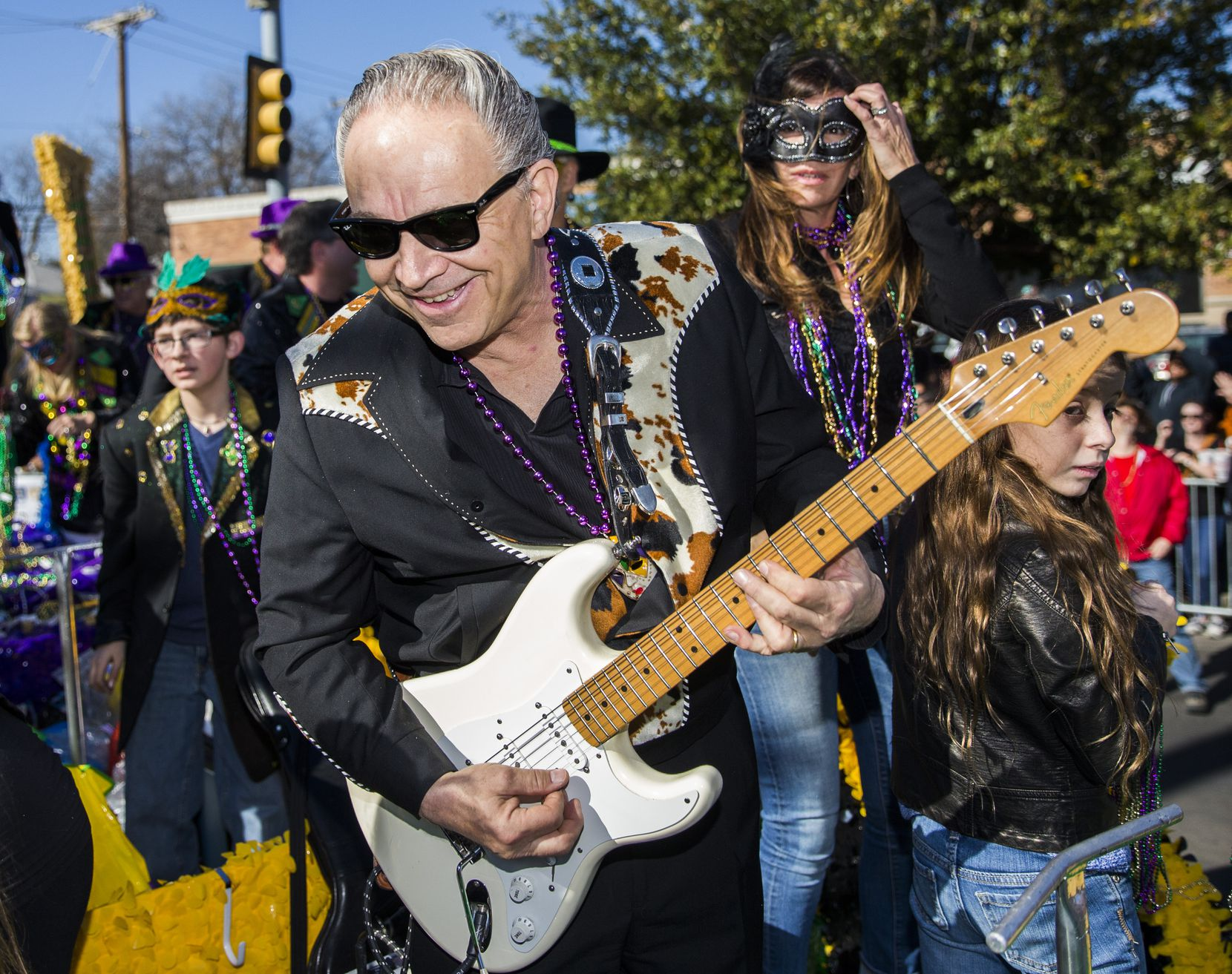 Musician and parade Grand Marshal Jimmie Vaughan plays his guitar on a float during the annual Oak Cliff Mardi Gras parade on Sunday, Feb. 7, 2016 in the Oak Cliff neighborhood in Dallas.