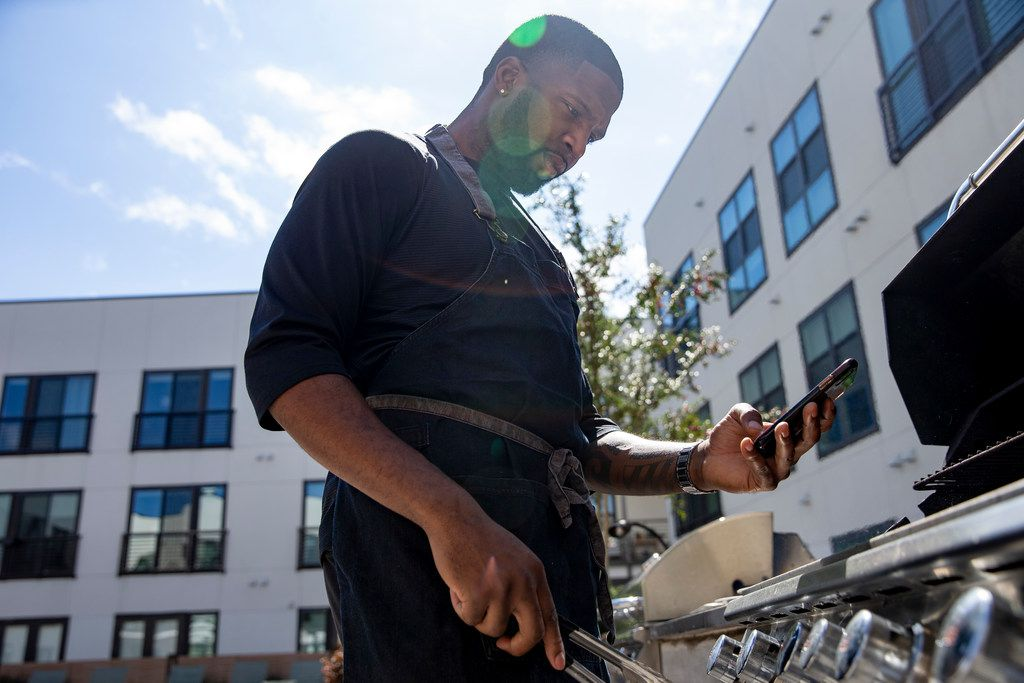Chef Kev Ashade takes a video as he prepares his chicken and beef suya at his Dallas home.