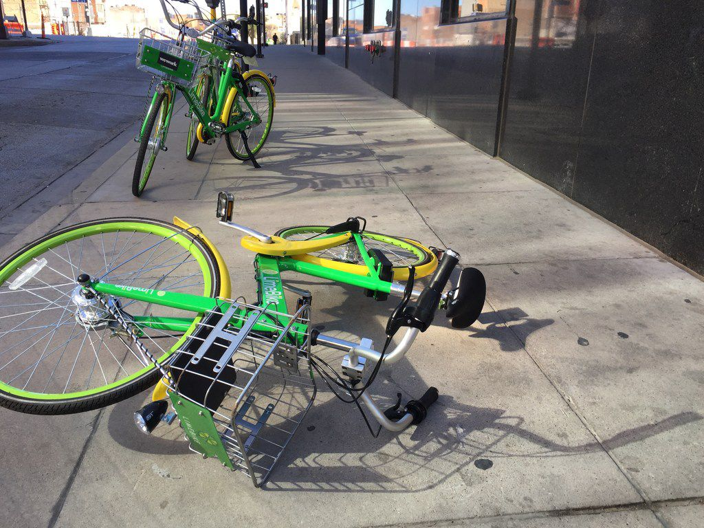 A LimeBike lies on a sidewalk on Harwood St in downtown Dallas, Texas on December 27, 2017.