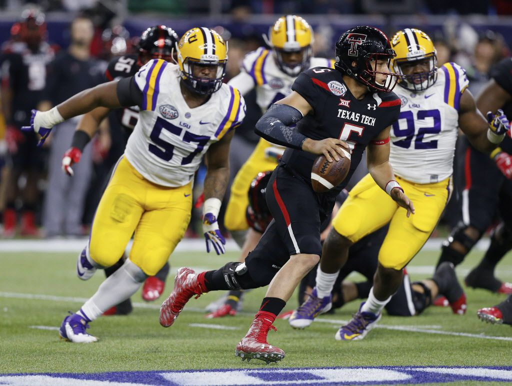 Texas Tech quarterback Patrick Mahomes (5) runs out of the pocket as he receives pressure from LSU defensive tackle Davon Godchaux (57) and defensive end Lewis Neal (92) during the first half of the Texas Bowl NCAA college football game Tuesday, Dec. 29, 2015, in Houston.