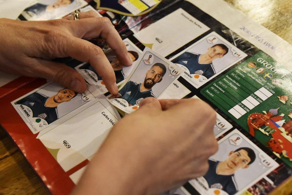 Una mujer pega la estampa de Javier Aquino, de la selección de México en su álbum mundialista en el restaurante Arepa TX.BEN TORRES/Especial para DMN