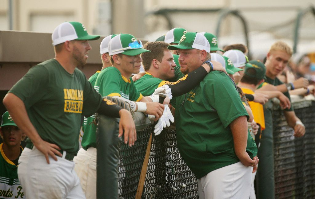 Santa Fe baseball members embrace before the second game of the best-of-three series in the Class 5A Region III playoff high school baseball game between Santa Fe and Kingwood Park at Jim Kethan Field at Deer Park High School in Deer Park, TX Saturday May 19, 2018. On Friday morning, 10 people were killed and 13 were injured after a shooting at Santa Fe High School. The game was postponed to Saturday after it was scheduled for Friday. Dimitrios Pagourtzis was booked into the Galveston County Jail on capital murder charges.