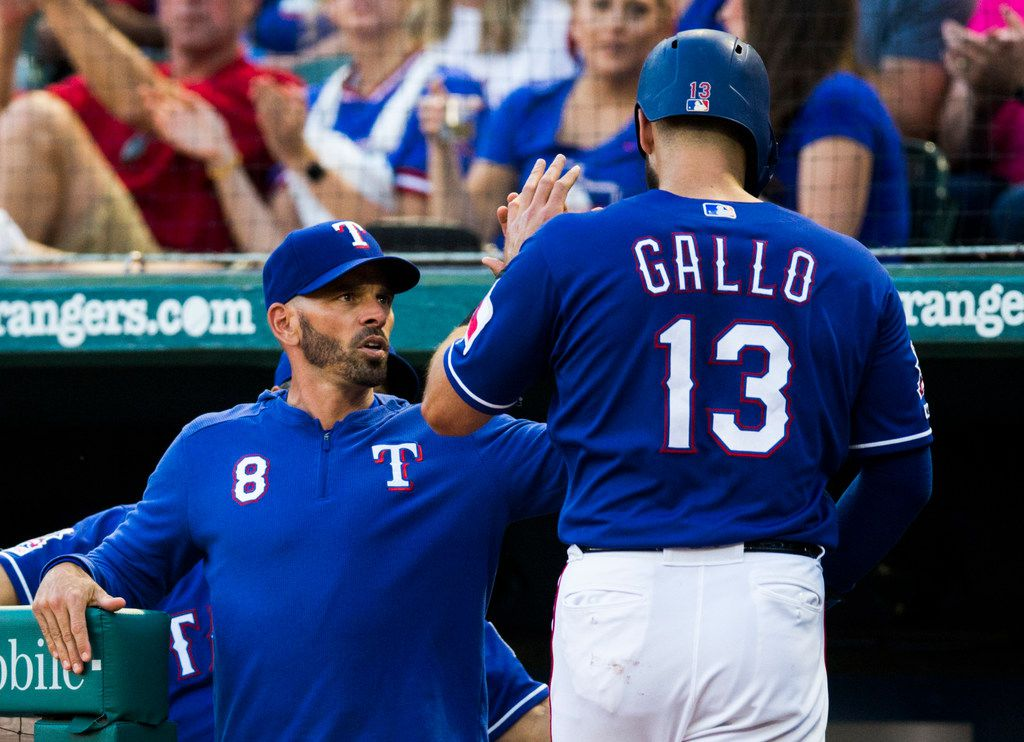 Texas Rangers center fielder Joey Gallo (13) gets a high-five from manager Chris Woodward (8) after Gallo scored a run during the second inning of an MLB game between the Texas Rangers and the Seattle Mariners on Tuesday, May 21, 2019 at Globe Life Park in Arlington. (Ashley Landis/The Dallas Morning News)