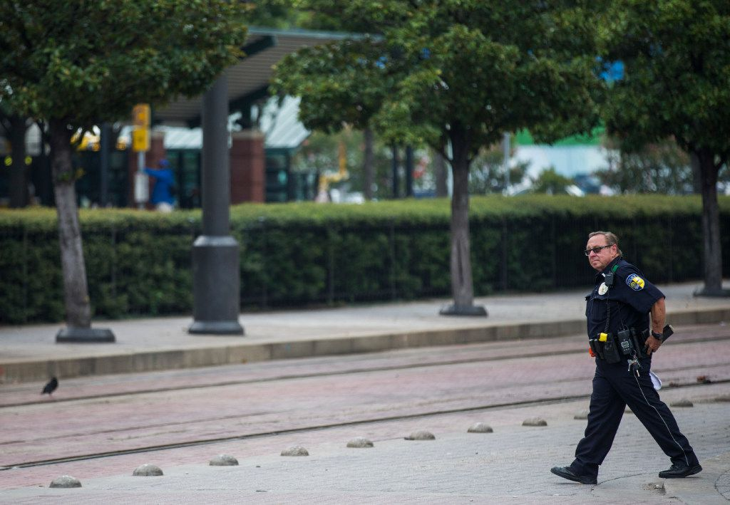 A DART officer walks across the tracks at the West End DART station on Aug. 3 in downtown Dallas.
