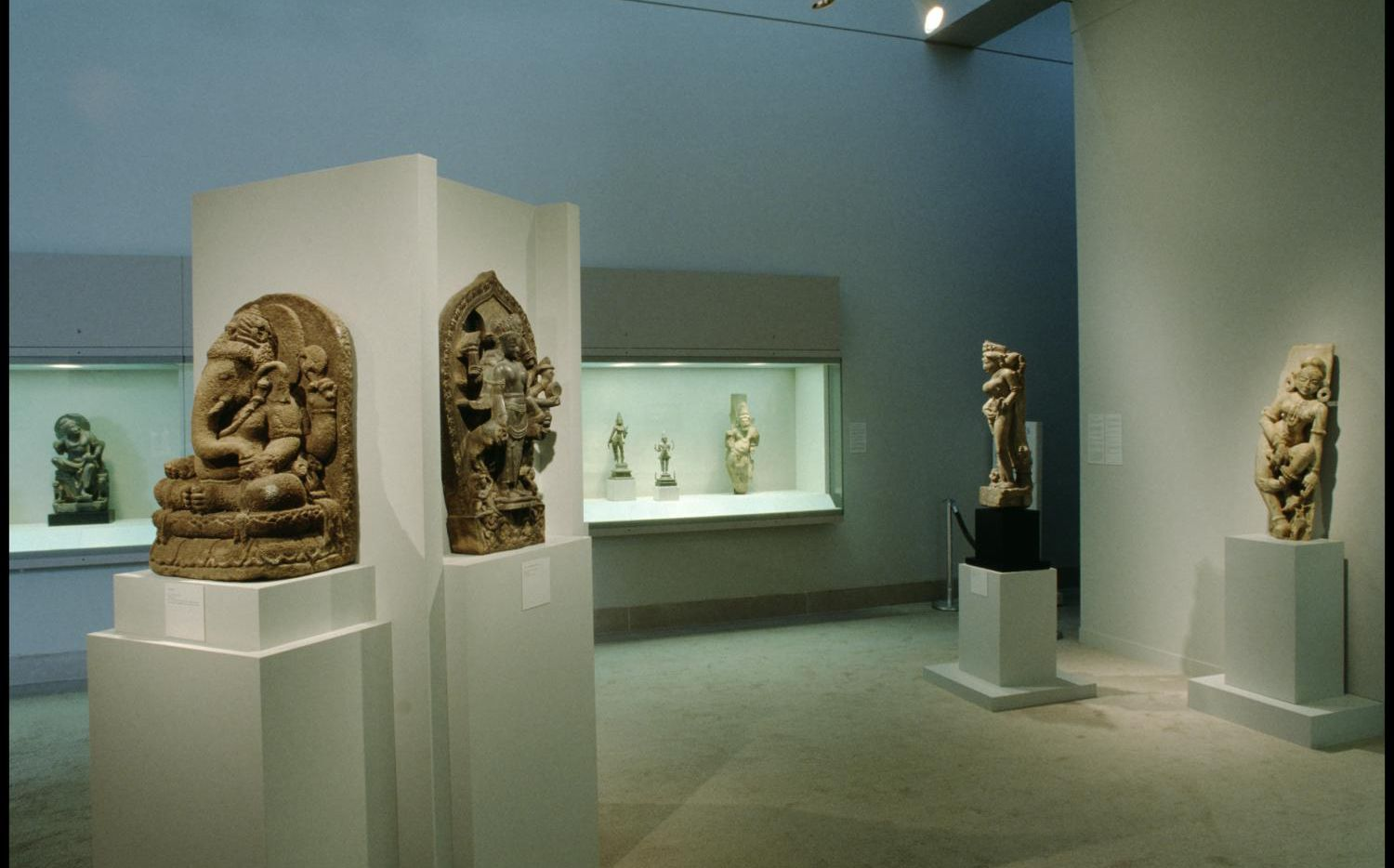 """A Lakshmi-Narayana stele from Nepal (foreground, center left) is shown on display in the exhibition """"East Meets West: Sculpture from the David T. Owsley Collection"""" from 1993 to 1994 at the Dallas Museum of Art. The DMA removed the stele from display in late 2019 in response to concerns about the provenance of the artwork."""