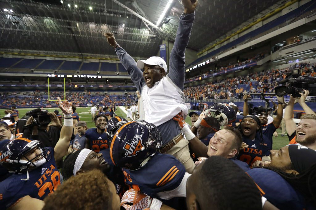 UTSA head coach Frank Wilson is lifted by his players as they celebrate their win over Charlotte in an NCAA college football game, Saturday, Nov. 26, 2016, in San Antonio. UTSA won 33-14, making them bowl eligible for the first time in the history of their football program. (AP Photo/Eric Gay)