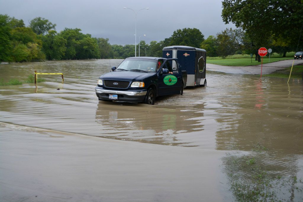 A pickup hauling a trailer drives through waters flooding out of the banks of White Rock Creek on Saturday in Dallas.