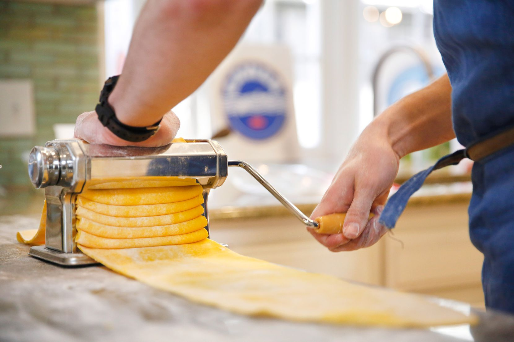 """Restaurant owner and chef Julian Barsotti uses a pasta machine to thin the lasagna sheets down to a 1/16"""" before boiling them. (Tom Fox/The Dallas Morning News)"""