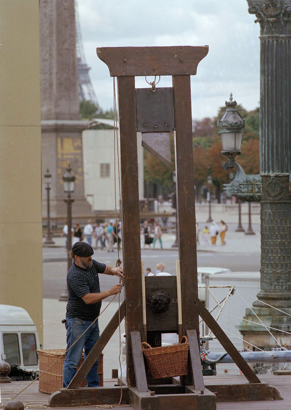 The head of a stuffed dummy emerges from the guillotine blade ready to be chopped off on Place de la Concorde in Paris, Aug. 20, 1988, as a worker sets its pulleys. The device was installed for the filming of a TV series on the French Revolution, at the very spot it was used 200 years ago.