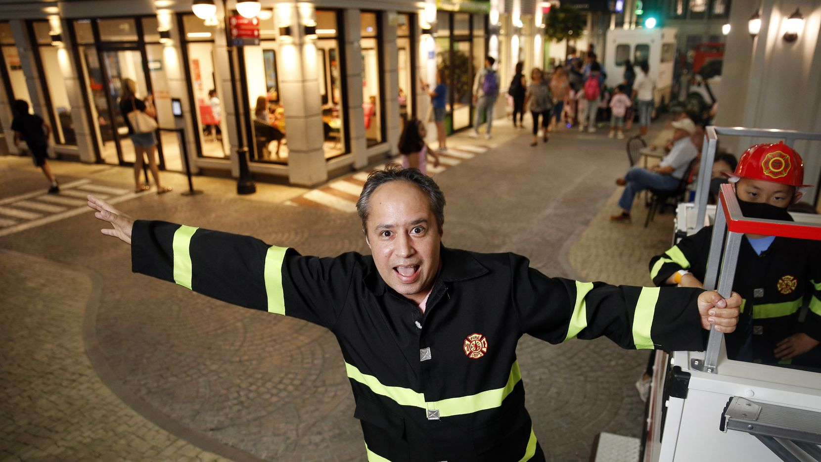 KidZania USA's chief of staff and business liaison officer Enrique Mena poses on the back of a kid-sized fire truck at their only United States location at Stonebriar Centre in Frisco, Texas, July 16, 2021.  Kidzania is an entertainment/interactive theme park for children ages 4-14. The two story location has 100 activities in 40 kid-sized store fronts. (Tom Fox/The Dallas Morning News)