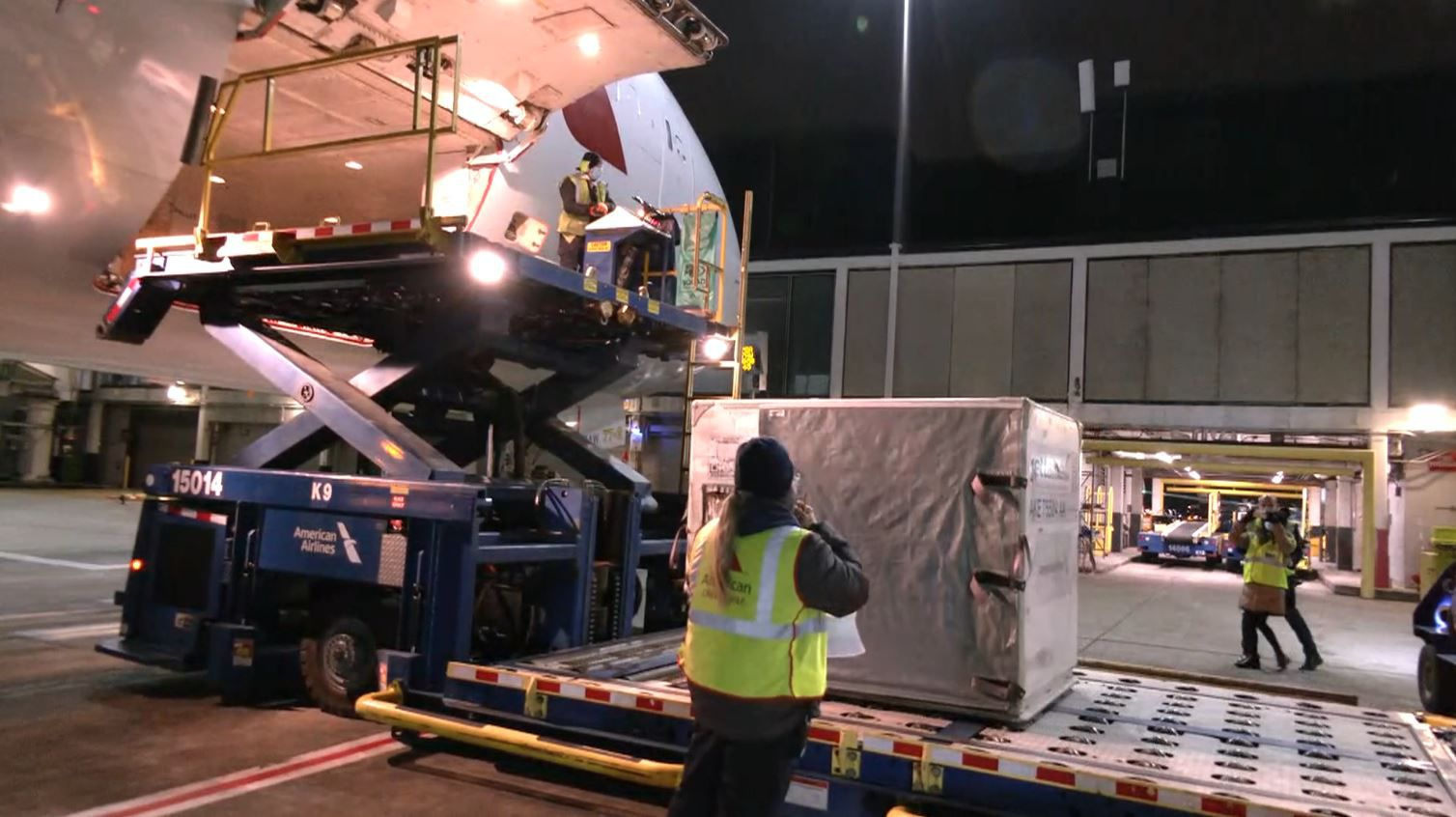 American Airlines workers at Chicago O'Hare International Airport load temperature-controlled shipments of COVID-19 vaccinations headed to Miami that will eventually go to a U.S. territory in the Caribbean.