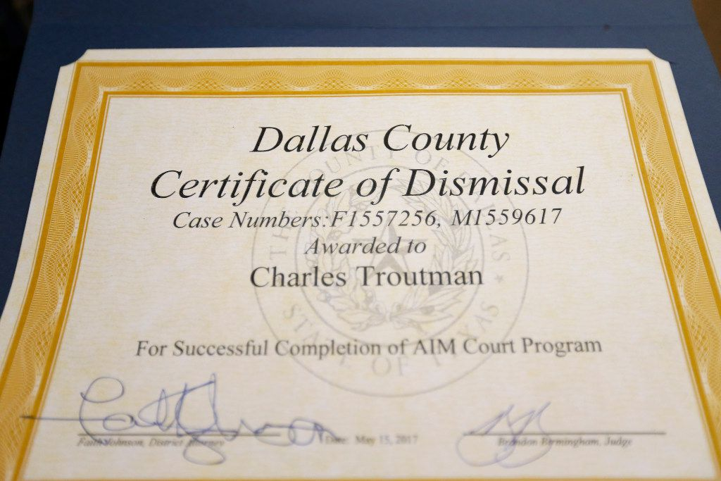 Charles Troutman shows his Certificate of Dismissal  after a graduation ceremony of the Achieve Inspire Motivate program at 292nd Judicial District Court in Dallas, Monday, May 15, 2017. He was charged with Impersonating a Public Servant in 2015 and his case has been dismissed after he completed the program. (Jae S. Lee/The Dallas Morning News)