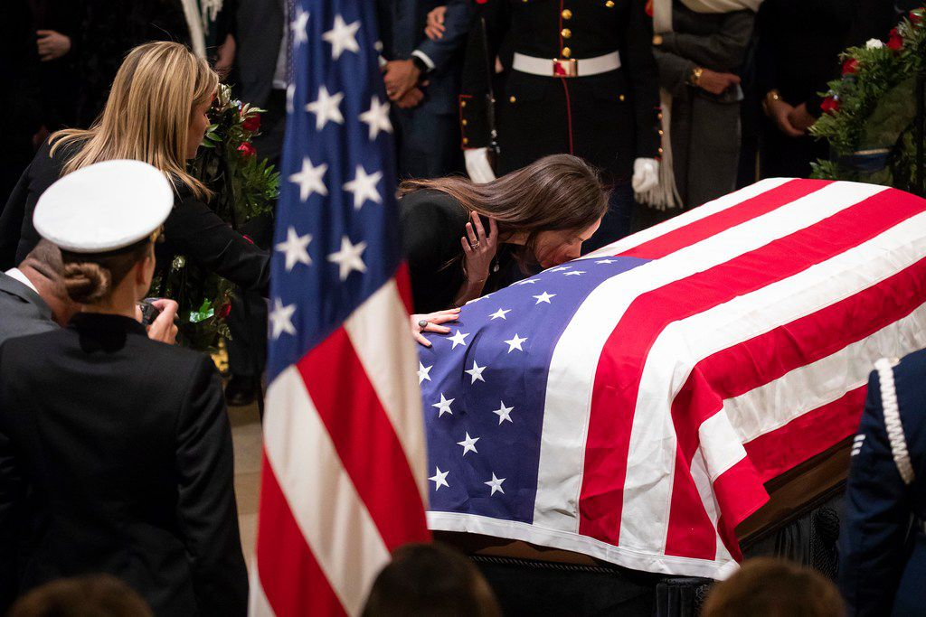 Barbara Pierce Bush kisses the flag-draped casket of her grandfather President George H.W. Bush as he lies in the Rotunda of the U.S. Capitol on Dec. 4, 2018, in Washington, D.C.