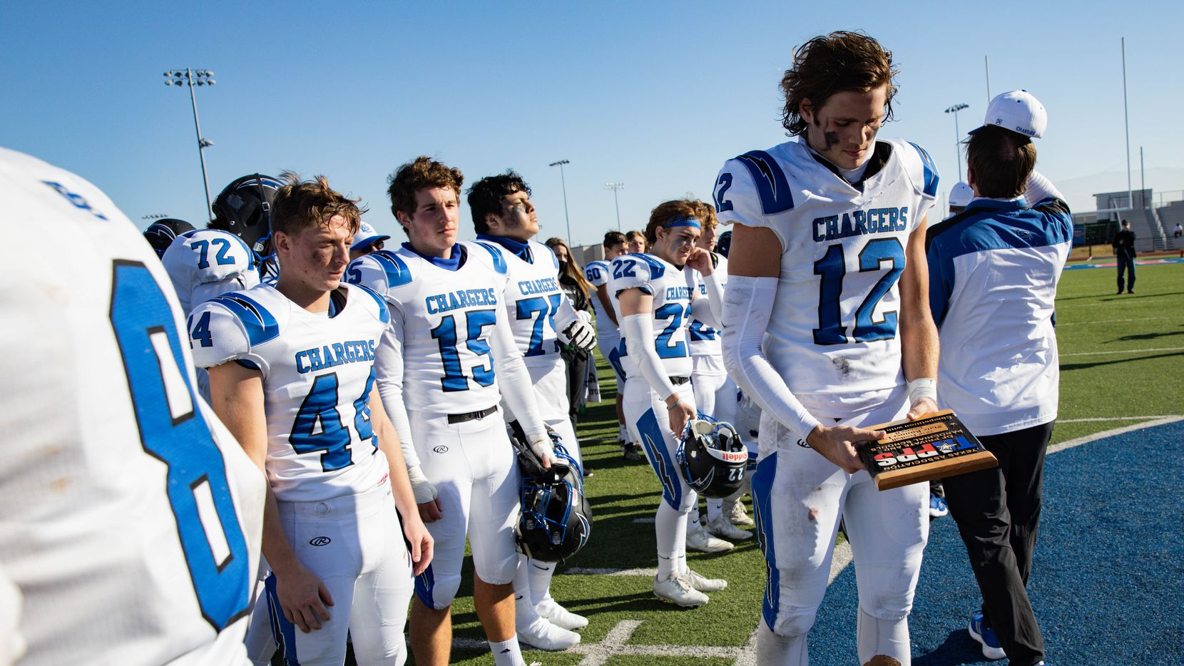 Dallas Christian player Brett Judd (12) holds the runner-up plaque after losing to Austin Regents following a TAPPS Division II state championship game against in Hewitt on Saturday, Dec. 19, 2020. Austin won with a touchdown in the final second, 26-20.