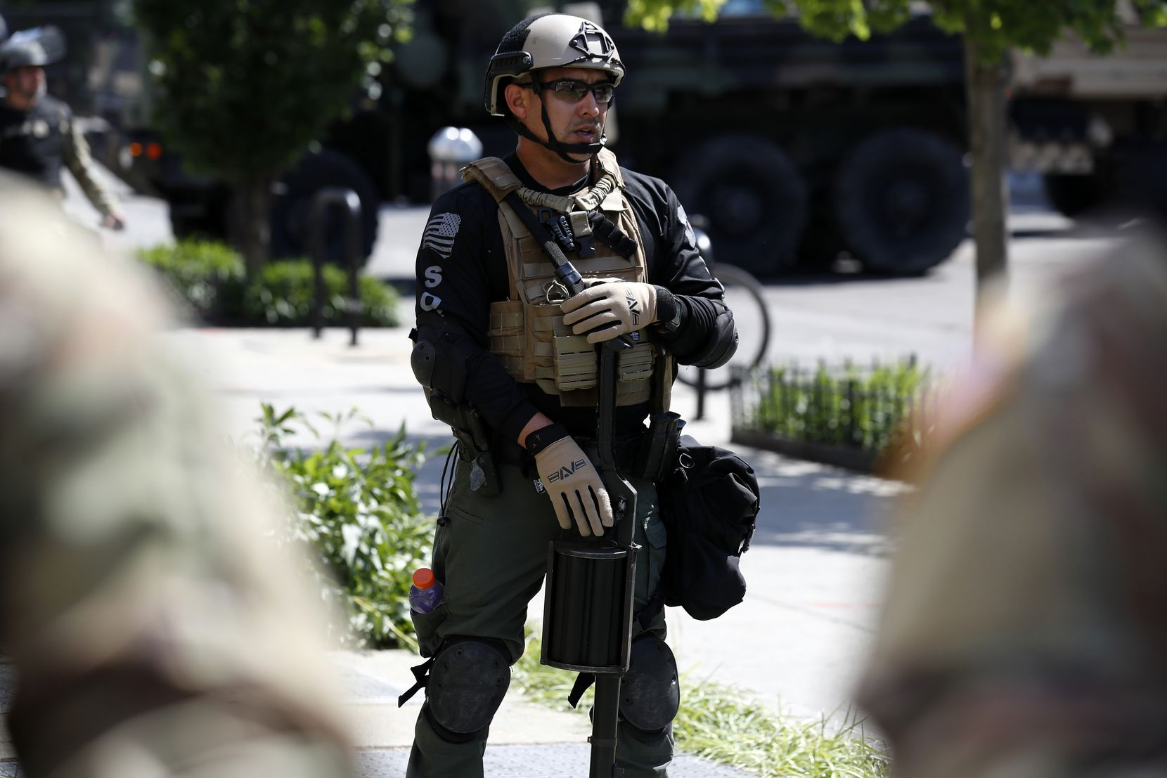 An officer from the Bureau of Prisons special operations response team carries a less-than-lethal weapon as demonstrators gather to protest the death of George Floyd on Wednesday, June 3, 2020, near the White House. Floyd died after being restrained by Minneapolis police officers.