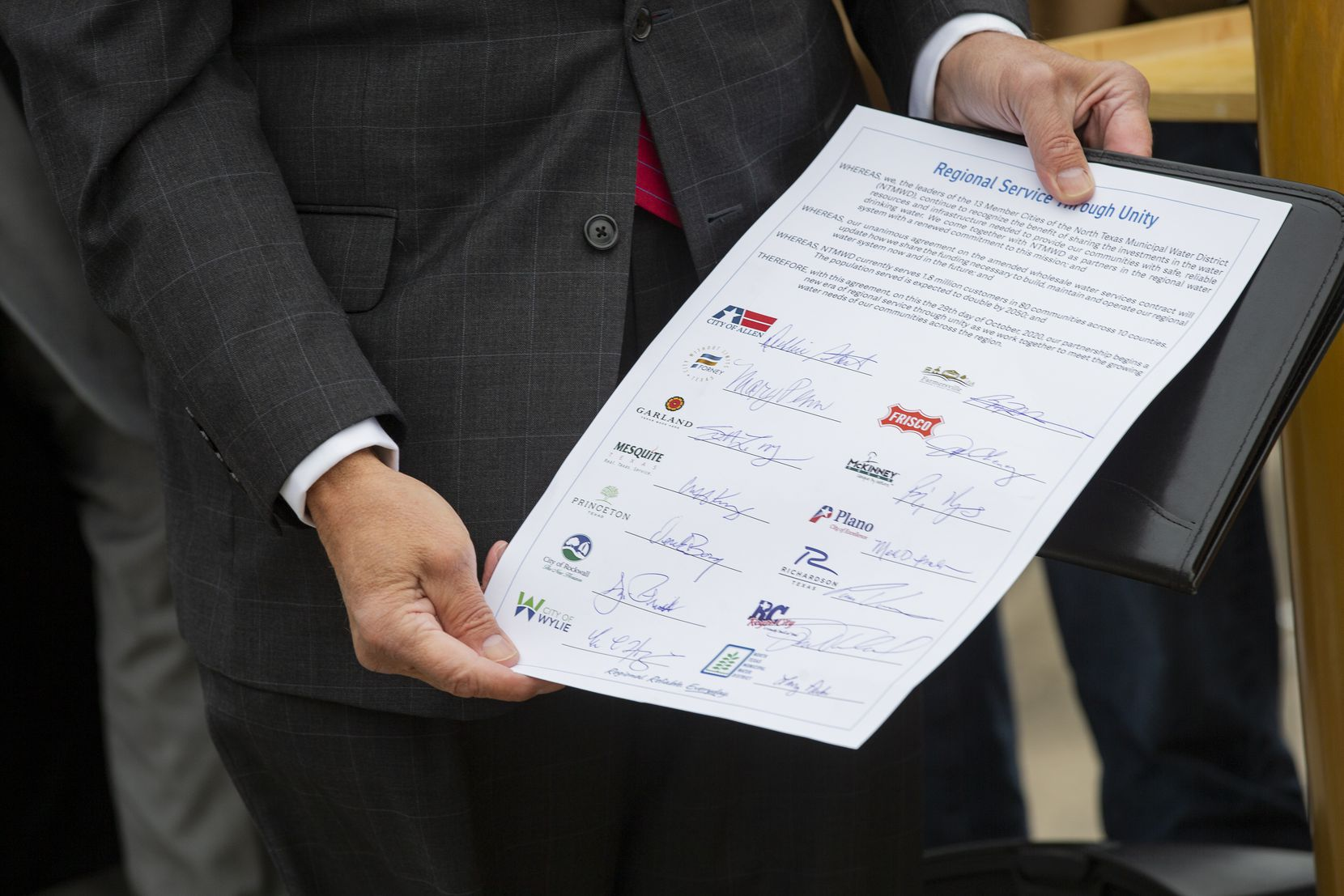 North Texas Municipal Water District board president Larry Parks holds the agreement signed by the district's 13 member cities Thursday. The also officially ends the rate case that the granddaddy suburbs of Plano, Richardson, Garland and Mesquite filed with the Public Utility Commission.