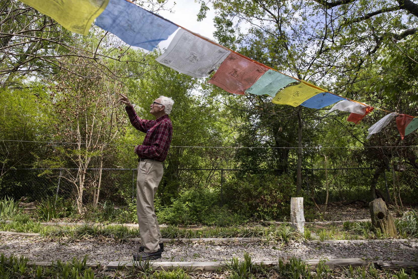 The Rev. Timothy Gollob walks past a line of prayer flags in the backyard of his Oak Cliff home as he identifies one of the multitude of birds that come to his many feeders.