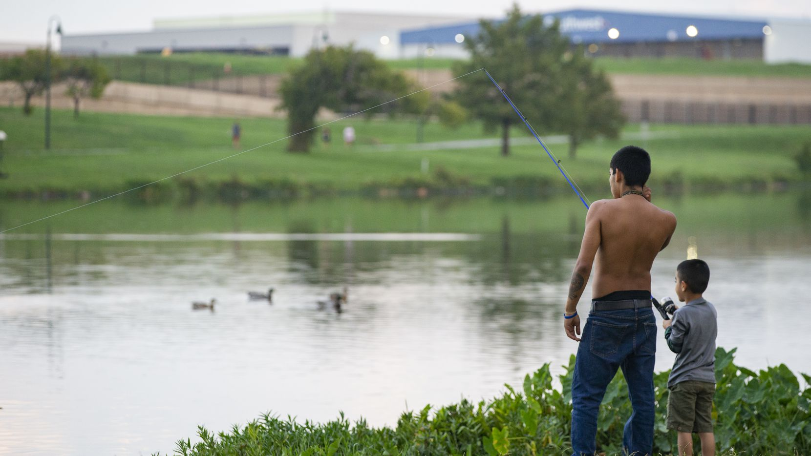Terrance Hunt shows son Milton Smith Ceren Mejía how to fish as they stand on the northern side of Bachman Lake Park. Under one of the conceptual designs on the short list of alternate Love Field entrances, a bridge might be built across this area of the lake to connect Northwest Highway and the airport.