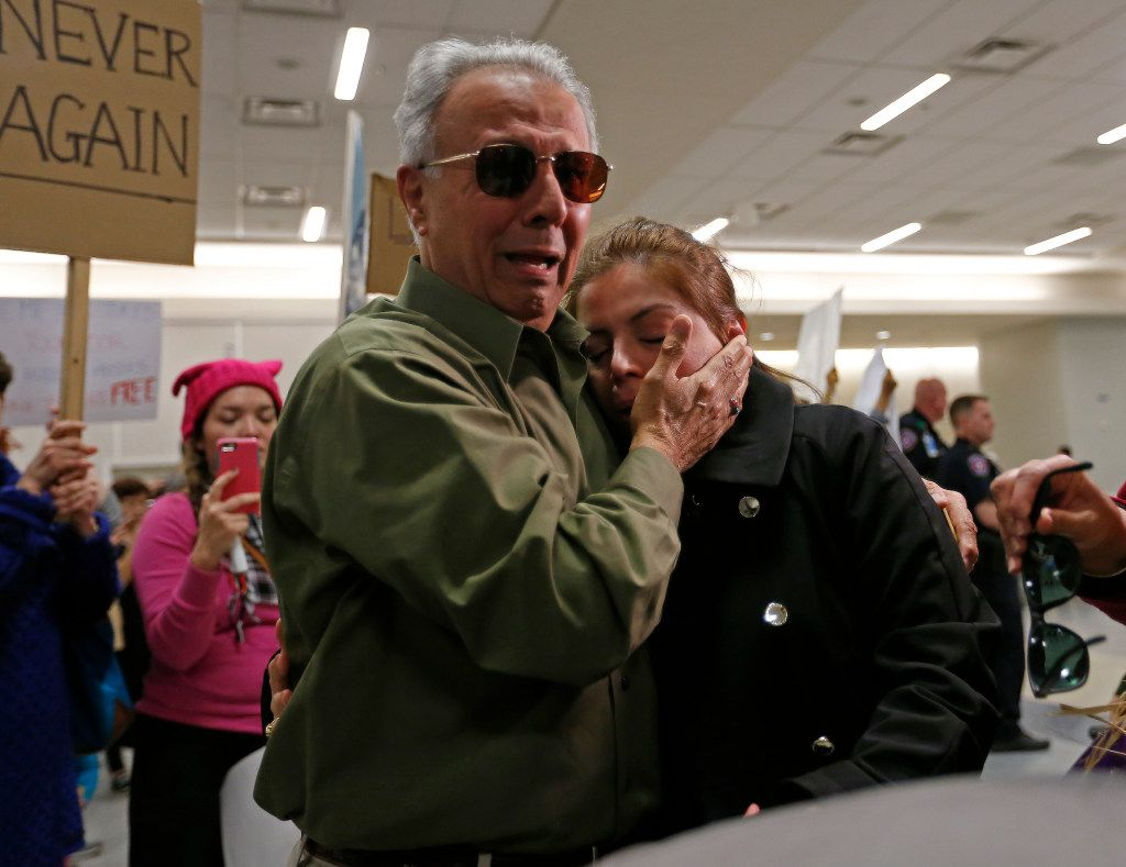 Shima Behgooy, a green card holder from Iran, cries on the shoulder of her father-in-law Ahmad Behgooy after she was held at DFW International Airport on Saturday. Shima's husband is a U.S. citizen. Her mother who was on the flight from Iran was sent back to Iran when they landed in Frankfurt, Germany.