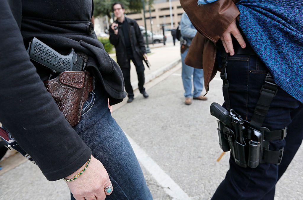 Dos personas muestran las pistolas que portan en fundas, durante una demostración frente al Capitolio de Austin, Texas.