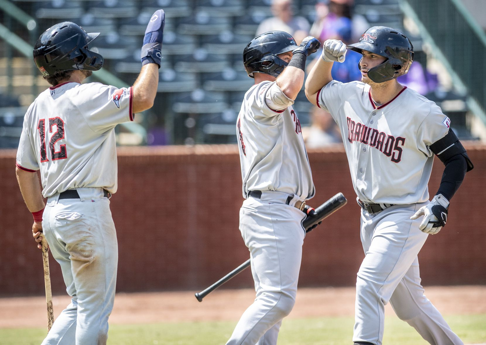 Hickory Crawdad's Justin Foscue (20), right, gets high fives from teammates Josh H. Smith (12), left, and Trey Hair (6), middle, after hitting a homerun during the game with the Greensboro Grasshoppers at First National Bank Field on Sunday, August 8, 2021 in Greensboro, N.C.
