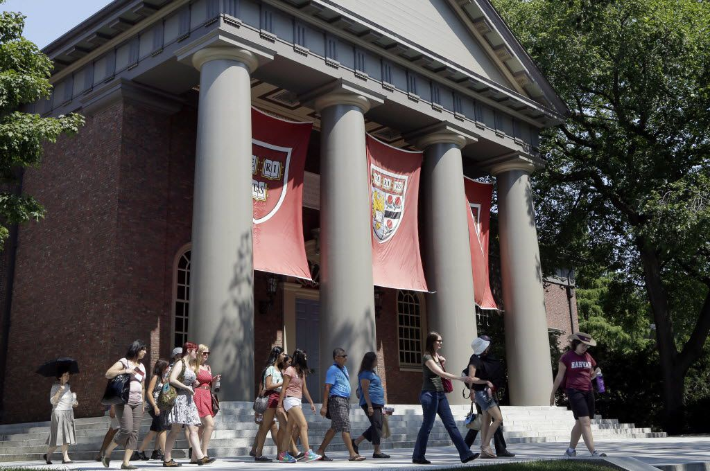 People are led on a tour on the campus of Harvard University in Cambridge, Mass.