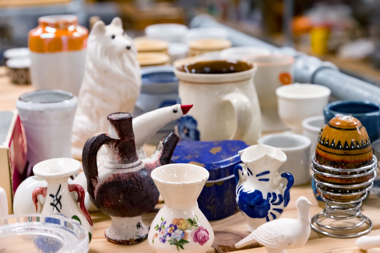 A collection of secondhand crockery and vases at a garage sale.