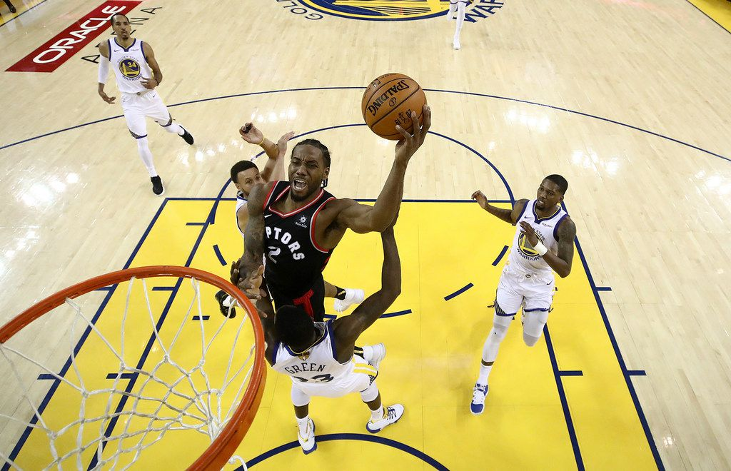 Toronto Raptors forward Kawhi Leonard, center, shoots against the Golden State Warriors during the first half of Game 3 of basketball's NBA Finals in Oakland, Calif., Wednesday, June 5, 2019. (AP Photo/Ezra Shaw, Pool)