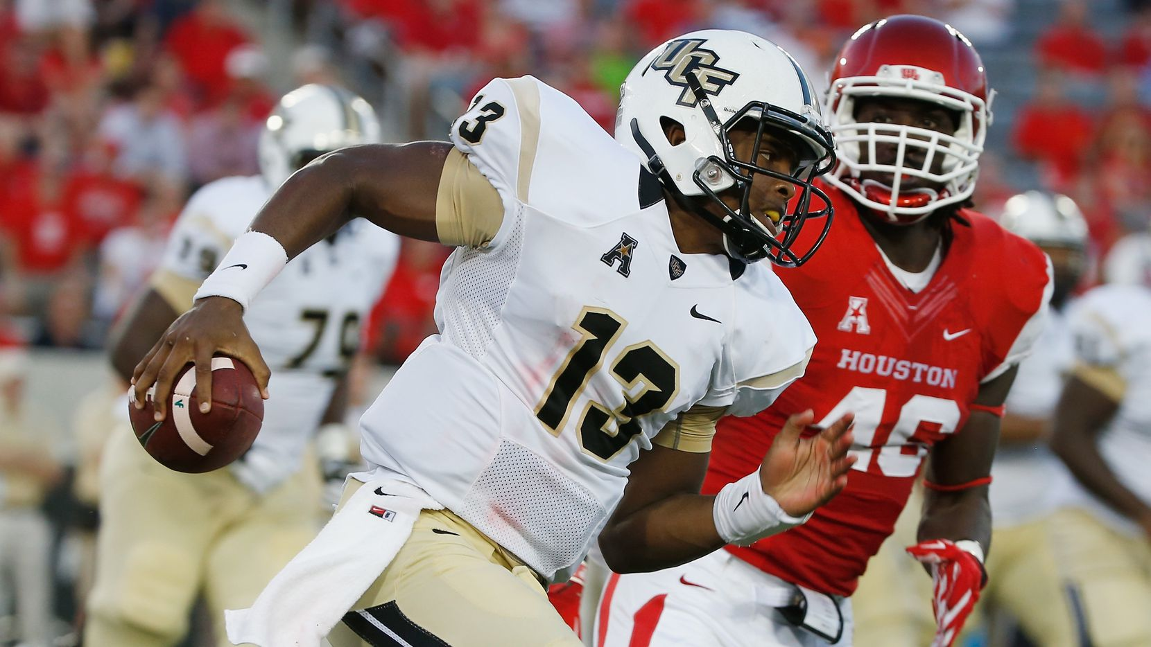 HOUSTON, TX - OCTOBER 02:  Justin Holman #13 of the UCF Knights scrambles in the first half past Trevor Harris #46 of  the Houston Cougars at TDECU Stadium  on October 2, 2014 in Houston, Texas.  (Photo by Scott Halleran/Getty Images)