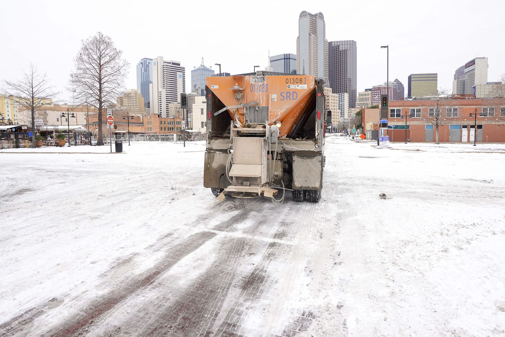 A City of Dallas Mobility and Street Services truck spreads de-icing materials downtown a winter storm brought snow and freezing temperatures to North Texas on Tuesday, Feb. 16, 2021, in Dallas. Another winter storm could dump 5 more inches of snow on Dallas-Fort Worth. (Smiley N. Pool/The Dallas Morning News)