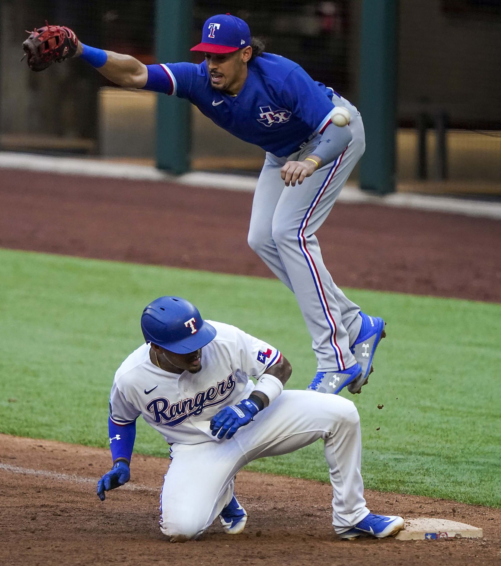 Infielder Andy Ibanez gets back to the base as the throw from right field gets away from first baseman Ronald Guzman on an attempt to double off Ibanez on a fly ball in an intrasquad game during Texas Rangers Summer Camp at Globe Life Field on Friday, July 17, 2020.