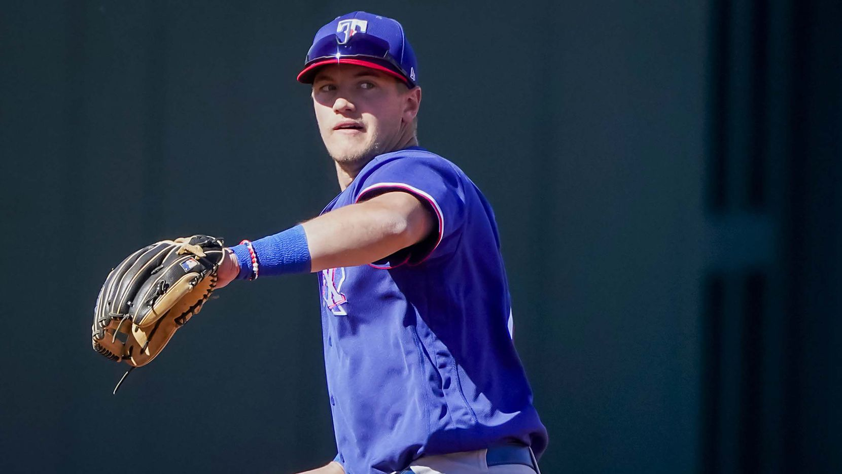 Texas Rangers infielder Josh Jung warms up at third base during the fifth inning of a spring training game against the Kansas City Royals at Surprise Stadium on Sunday, Feb. 28, 2021, in Surprise, Ariz.