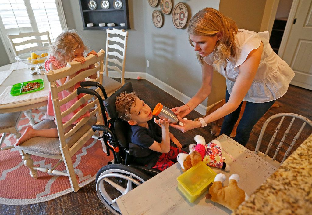 Kasey Woleben, right, holds a cup for son Will, as her daughter Lauren looks on at their home in McKinney, Texas. Will uses a feeding tube but his parents give him small tastes of food and drinks.