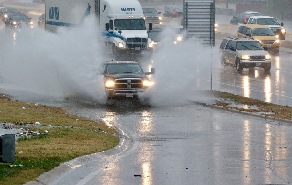 A truck splashes through standing rainwater at the Illinois Ave on north bound Interstate 35 in Dallas during Tuesday morning's rush hour on December 19, 2017. Storms are expected to continue throughout the day. (Irwin Thompson/Staff Photographer)